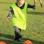 Boy in Bib Playing Football